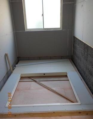 新しい防音室の防音壁に防音材を張る